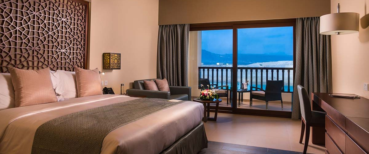 king bed with seating area and balcony view at deluxe room inside fanar hotel and residences hawana salalah