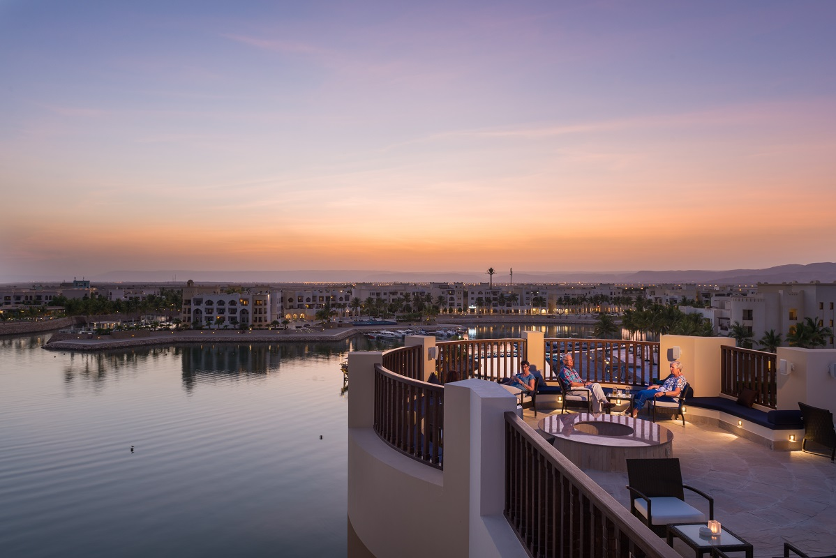 sunset marina view from fanar hotel in salalah roof area with guests setting at the roof area