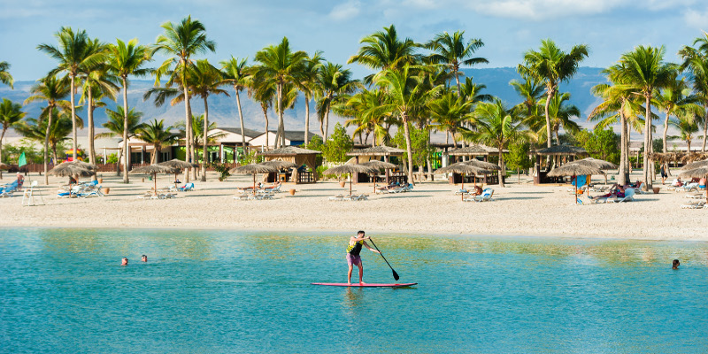 a guy with paddle board at hawana salalah resort beach with beach seating area view in oman