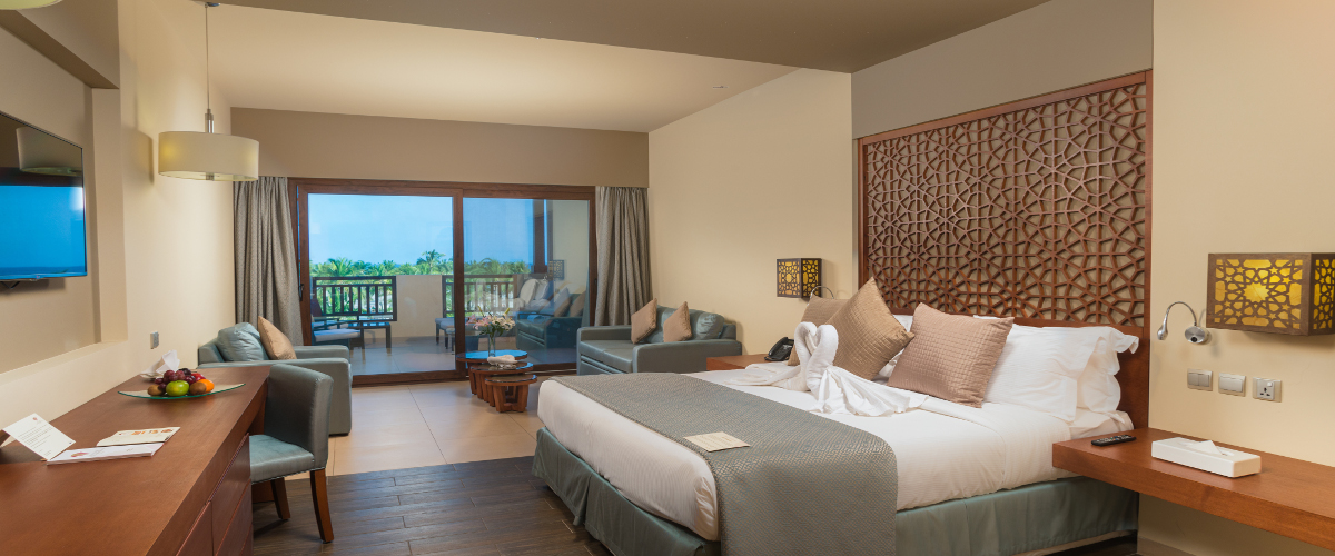 king bed with seating area and terrace area at family room inside fanar hotel in salalah oman