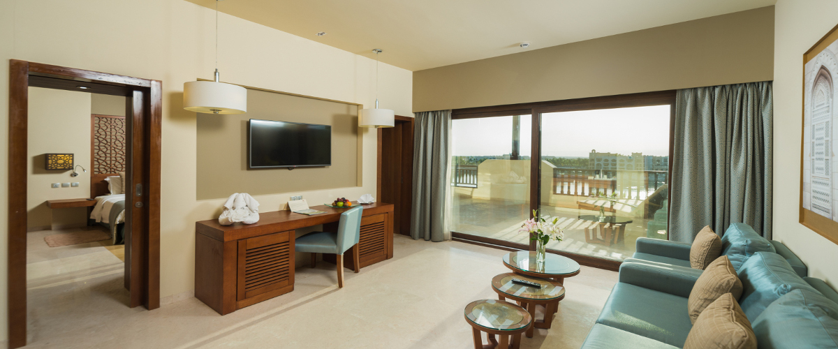 seating area and terrace area overlooking marina at deluxe suite in fanar hotel salalah