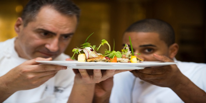 two chefs at fanar hotel in salalah holding a food plate
