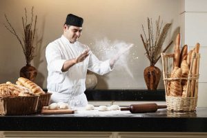 A chef is preparing a pizza for a pizza lesson as a fun activity at Fanar Resort in Salalah Oman