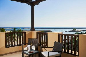 The outdoor terrace of marina suite furnished with 2 chairs and a small coffee table with Indian Ocean View at Fanar Hotel and Residences in Hawana Salalah Oman