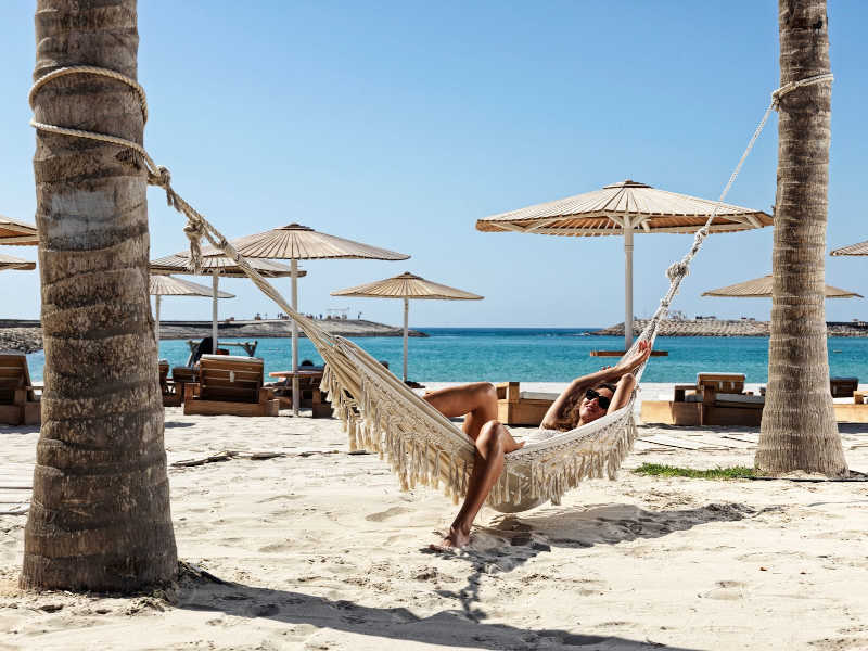A girl is enjoying the relaxation by sleeping in a hammock and breathing sea fresh air of ocean at Fanar Hotel and Residences in Hawana Salalah Oman