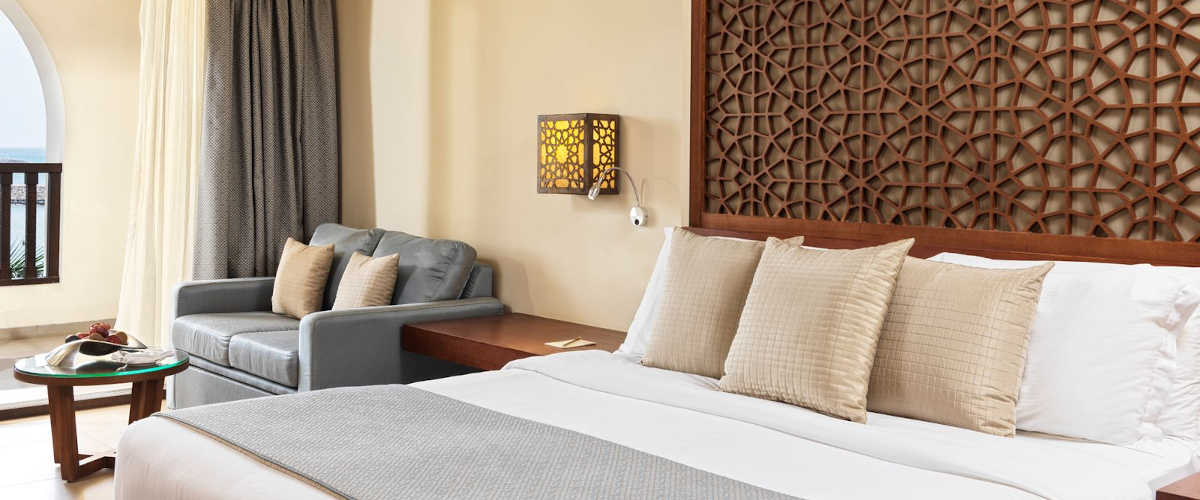 Deluxe Suite in brown beige painted walls that furnished with a king bed and a small sofa with coffee table and aside desk in Fanar Salalah 5 Stars Hotel in Oman