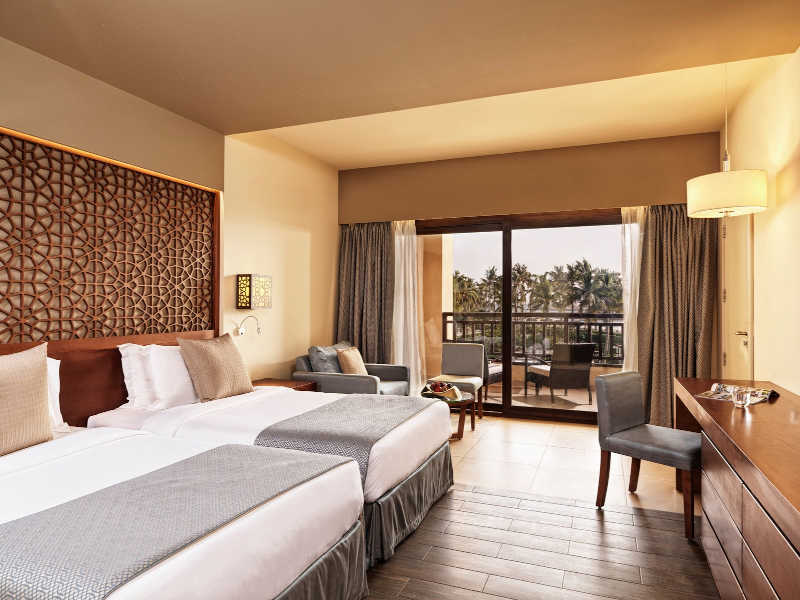 The overview of Deluxe Room of Fanar Hotel with ocean view that furnished with 2 twin beds in a brown grey theme in Oman