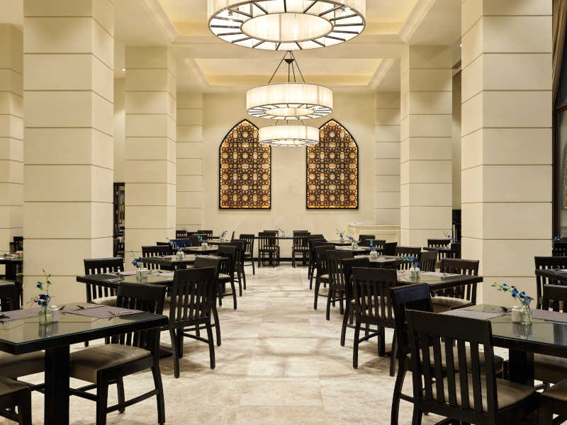 The dining tables in Al Souk restaurant that is serving themed buffets or a la carte menus at Fanar the luxury hotel in Hawana Salalah Oman