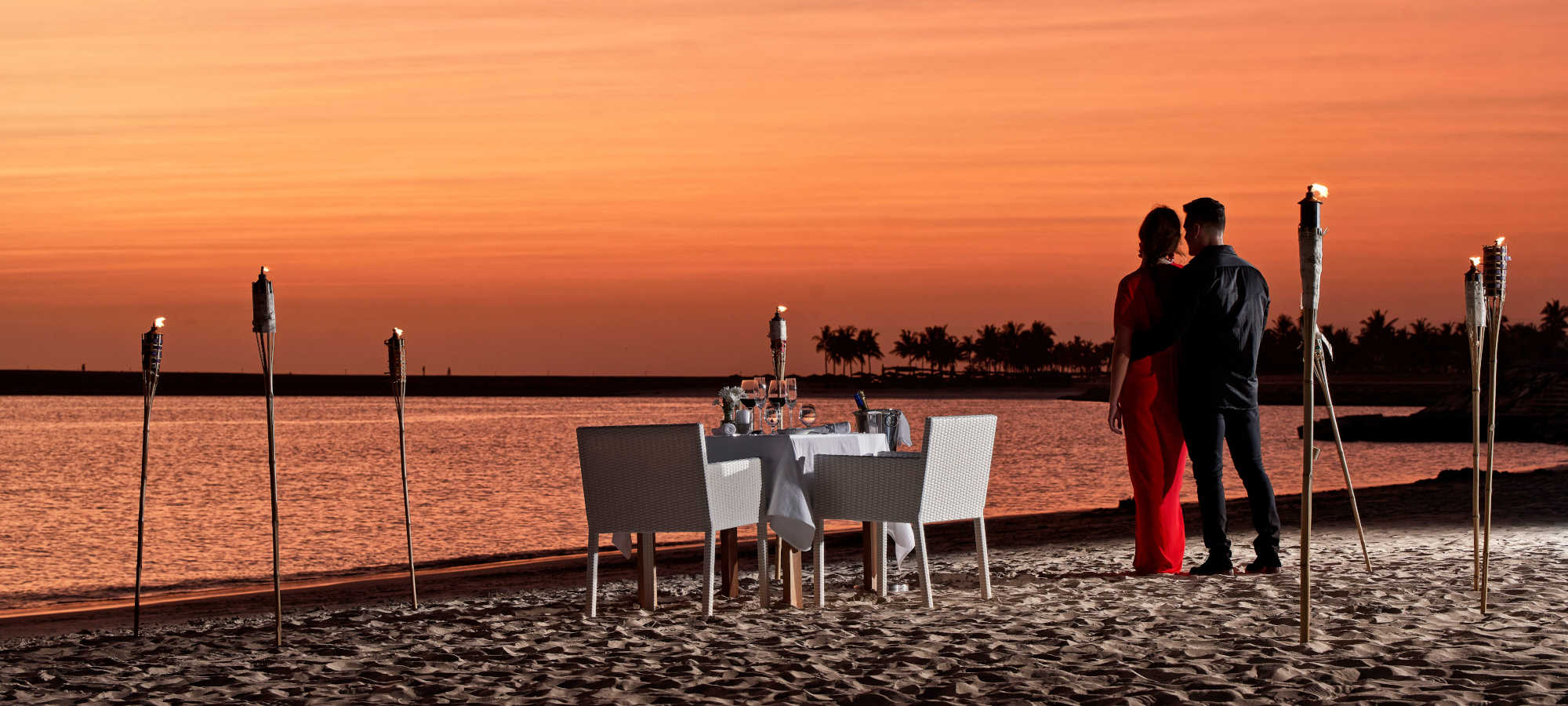 Fanar Hotel romantic dinner by the ocean and a couple who is enjoying the romantic vibes of the dinner with a magical view to the sky and the ocean in Hawana Salalah Oman