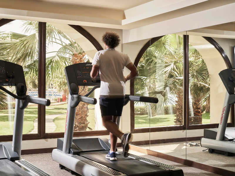 a guy is working out by running on a treadmill at the Gym that fully equipped in Fanar Resort in Hawana Salalah Oman