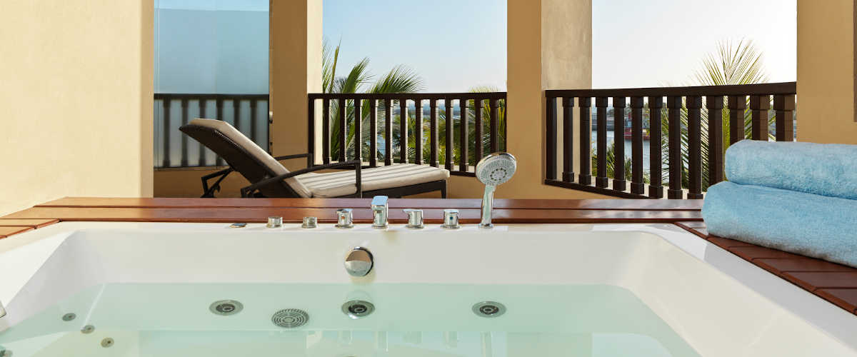 The terrace of Jacuzzi Suite with a view to ocean and a jacuzzi and a laid back bed at Fanar Resort in Hawana Salalah Oman