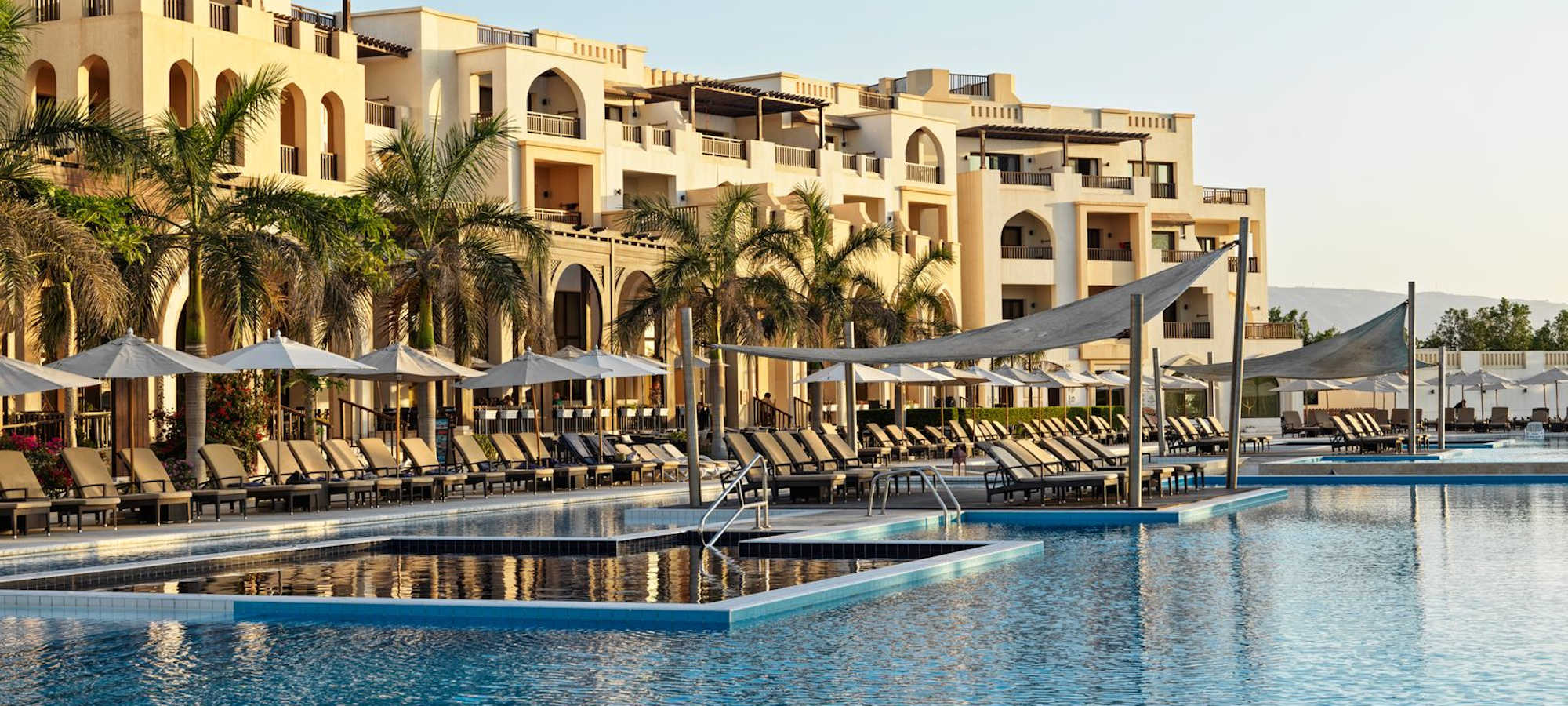 The main pool of Fanar Hotel and Residences surrounded by sunbeds and umbrellas in Salalah Oman