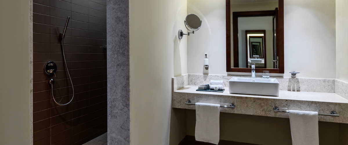 The bathroom of Marina Suite with bathtub and a wide mirror on the right and shower cabinet on the left in Fanar luxury resort in Salalah Oman
