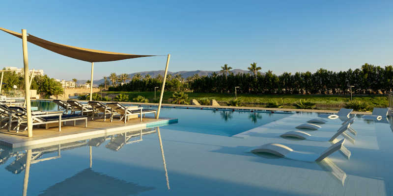 The luxury swimming pool of Fanar Hotel and 5 stars accommodation in Salalah Oman with a view to lavish green landscape