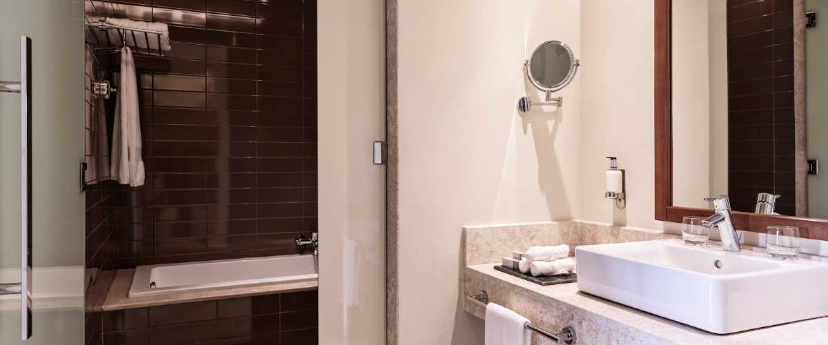 The bathroom of Fanar Deluxe Suite with bathtub and a wide mirror on the right and shower cabinet on the left in Fanar luxury resort in Salalah Oman