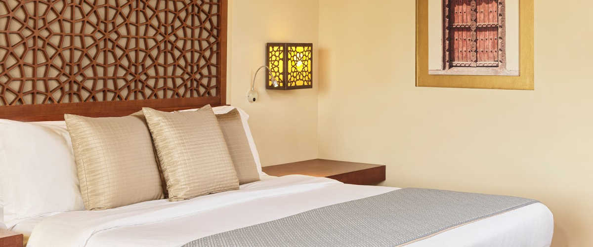 The comfortable king bed at Fanar Hotel Deluxe Suite in an arabian theme for accommodation in Hawana Salalah Oman