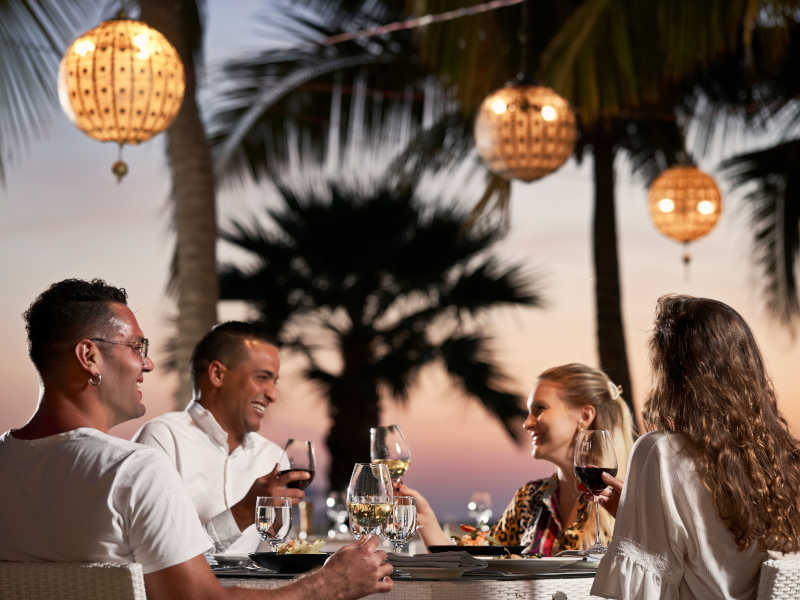 A group of friends are having dinner at the outdoor area of Aubergine Restaurant in Fanar Hotel and Residences with a Mediterranean theme to the cuisine