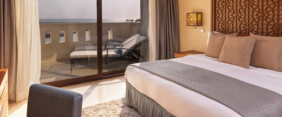 The deluxe suite bedroom furnished with luxury king bed and and a wide glass door to the terrace that has 2 sunbeds and ocean view at Fanar Hotel Hawana Salalah Oman