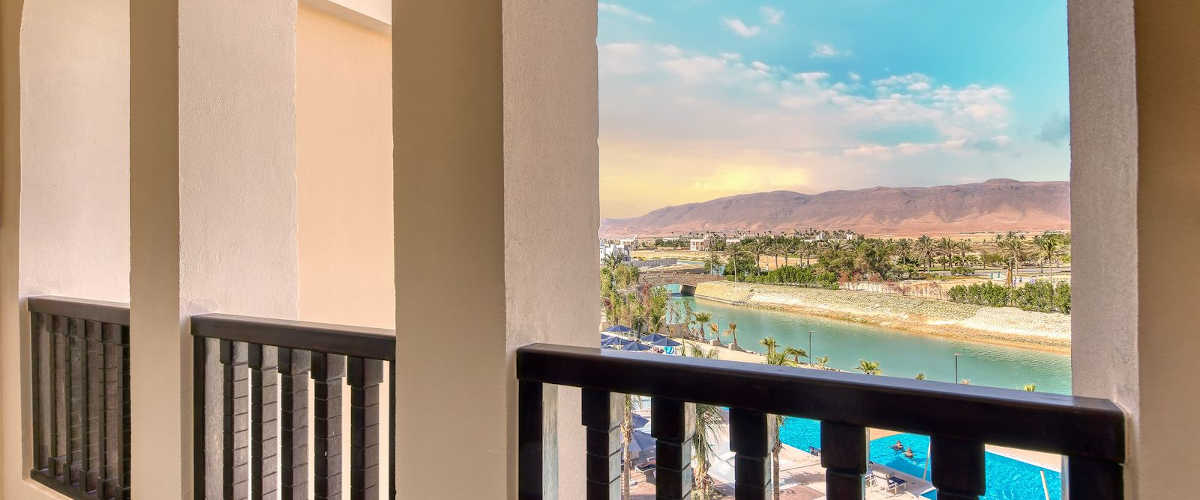 The view from deluxe room terrace that showing the magical blend of blue lagoons, mountains and lavish greenery landscape in Fanar Hotel & Residences in Hawana Oman