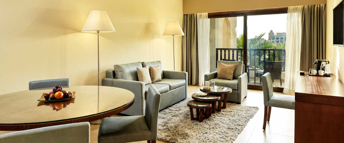 The spacious living room of Marina Suite at Fanar Resort furnished with a seating area, a writing desk and a dining table with a door to terrace in Oman
