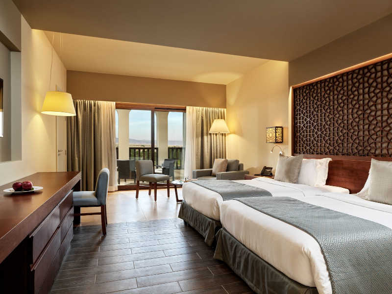 The spacious deluxe room that is furnished with twin beds and a seating area with a terrace in Fanar 5 Stars Hotel in Oman