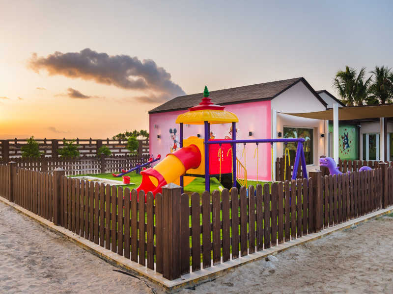 Kids Club at Fanar Hotel & Residences with a playground, slides and grass to be safe for children and surrounded by fence in Hawana Salalah Oman