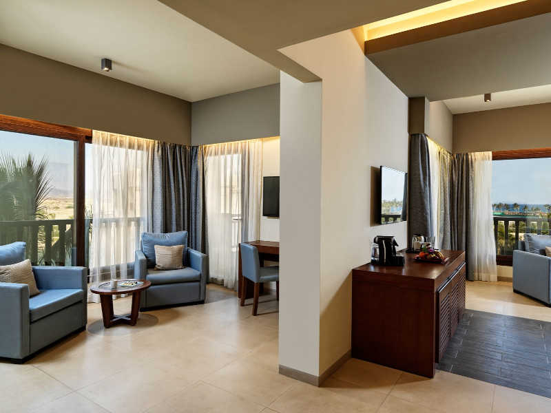 The spacious connected rooms in the best hotel for a family vacation in Fanar Hotel and Residences in Oman furnished with sofas, a writing desk and coffee amenities with a wide glass window around the place with a view to the ocean