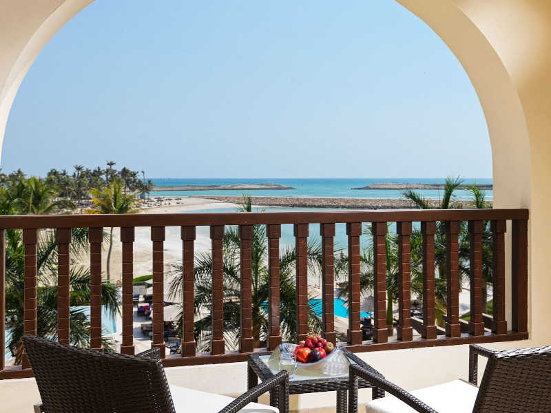 The view from Deluxe Room terrace with the turquoise water of ocean and palm trees in Fanar best resort in Hawana Oman